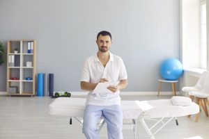 Young male doctor with clipboard sitting on hospital bed in office of new clinic