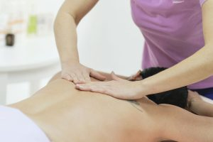 Physical Therapist Massaging the Back and Shoulder of a Female Patient. Over shoulder view of masseur performing deep tissue massage of womens back to release pain