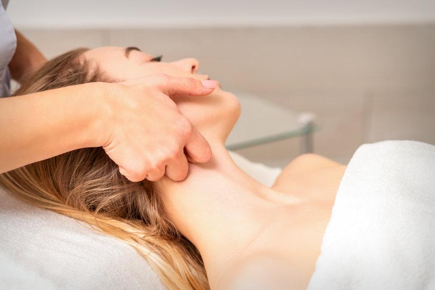 Beautician making lymphatic drainage face massage